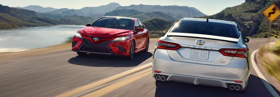 Two 2019 Toyota Camry models driving past each other on the road