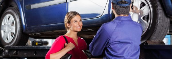Woman smiling at technician performing car tire maintenance